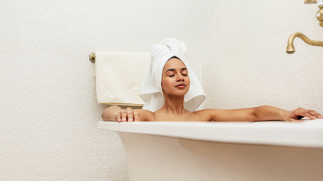 Woman with white towel on her head relaxing in bath with eyes closed