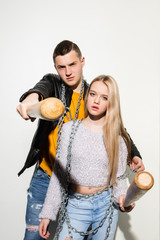 Sport games. Close up fashion portrait of two young cool hipster girl and boy wearing jeans wear. Woman and man with a baseball bats. Studio shot of two cheerful best friends having fun and making
