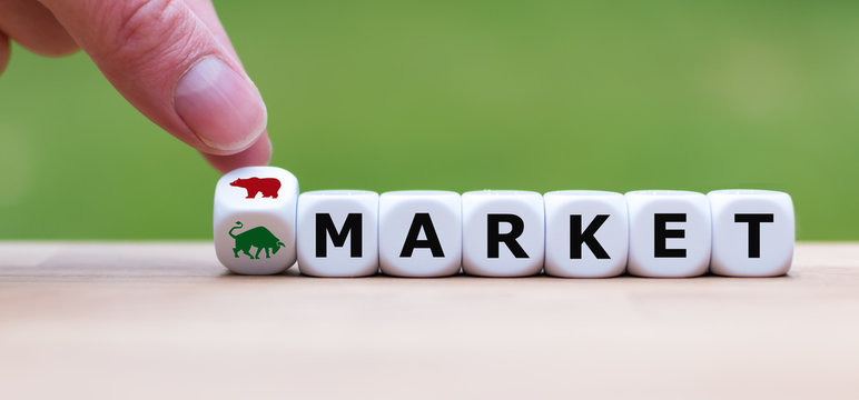 Symbol for a trend change at the stock market. Hand turns a dice and changes the symbol of a bear to a bull to indicate the change from the bear market to a bull market.