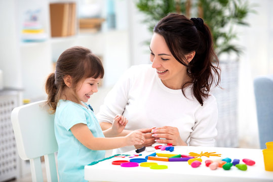 Smiling mother helps a little daughter to sculpt figurines from plasticine. Children's creativity. Happy family