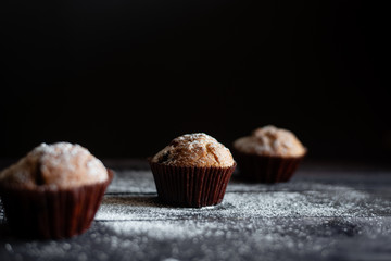 Three chocolate muffins on a wooden table a dark background. Place under the text
