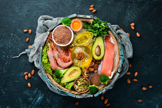 Food with natural vitamin Omega 3. Healthy food: fish, shrimp, broccoli, flax, nuts, egg, parsley. Top view. Free space for your text. On a black background.
