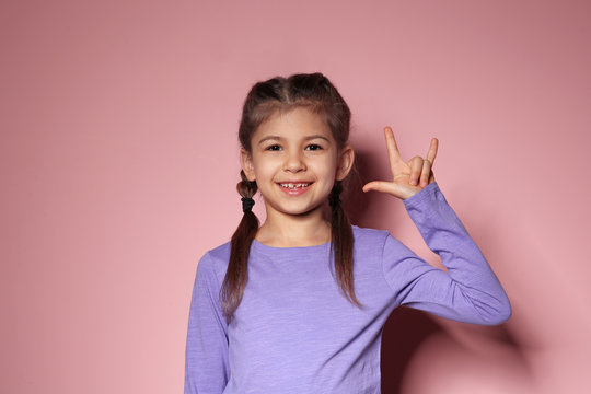 Little girl showing I LOVE YOU gesture in sign language on color background