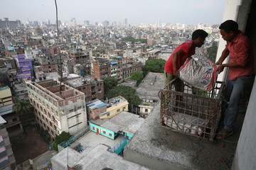 Workers without safety gear work on the edge of a building under construction in Dhaka