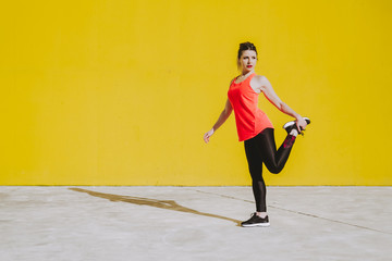 Young lady in sportswear stretching legs near yellow wall in sunny day