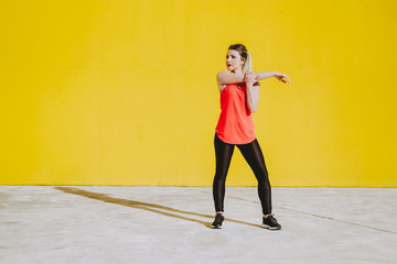 Young lady in sportswear stretching arms near yellow wall in sunny day