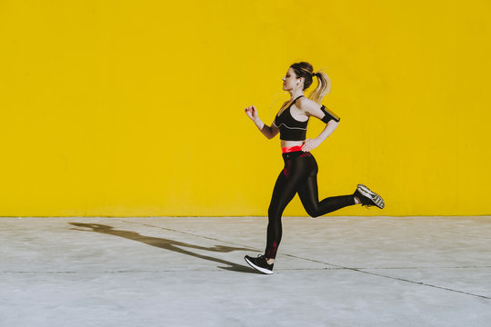 Side view of young lady in sportswear with earphones running near yellow wall in sunny day