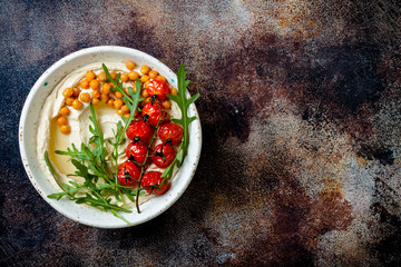 Homemade hummus with roasted cherry tomatoes. Middle Eastern traditional and authentic arab cuisine. Top view, copy space Fototapete