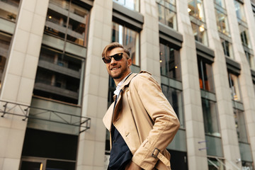 Man portrait. City style. Handsome man in trench coat and sun glasses is smiling while standing outdoors