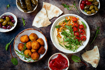 Arabic traditional cuisine. Middle Eastern meze with pita, olives, hummus, stuffed dolma, falafel balls, pickles. Mediterranean appetizer party idea Fototapete