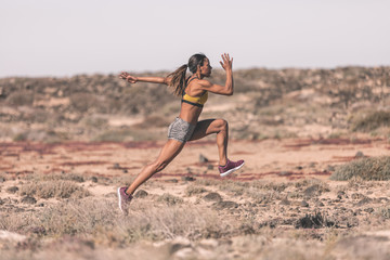 Ethnic sportswoman running on desert road