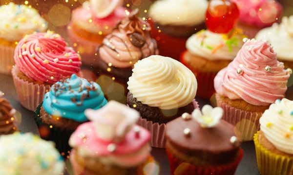 Tasty Colorful cupcakes on background