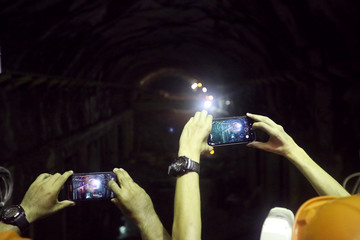 People take pictures with their cell phones inside the construction site of Hidroituango hydroelectric plant in Ituango