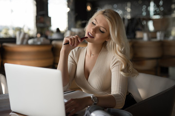 Sexy woman using laptop pc sitting in cafe