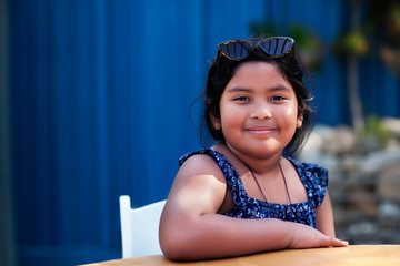 Portrait of a friendly little girl wearing shades and modest clothing while sitting and smiling in an outdoor setting.