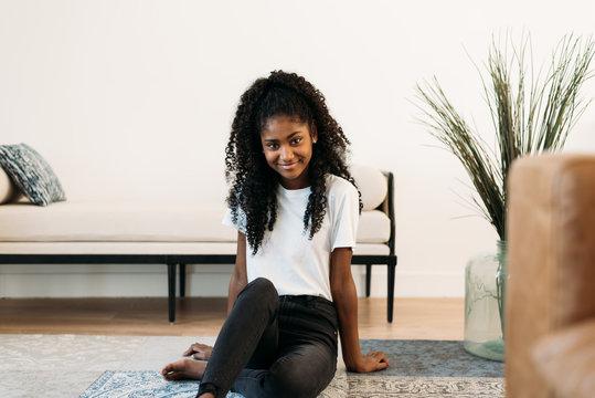 Beautiful young black teenage girl sitting in a rug