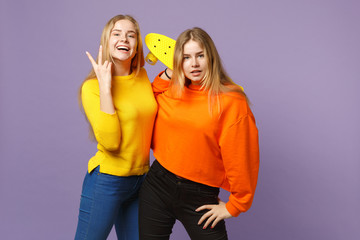Two cheerful young blonde twins sisters girls in vivid clothes showing victory sign, holding yellow skateboard isolated on violet blue background. People family lifestyle concept. Mock up copy space.