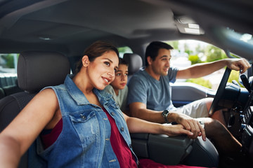 hispanic family with mother, father and son sitting in truck looking outside