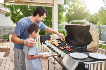 father teaching son how to grill hot dogs and bonding