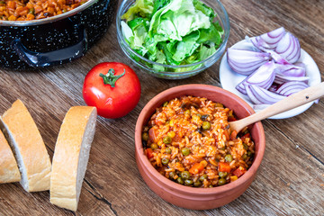 Fried rice with vegetables and spices in a vintage clay bowl and tomato, lettuce, onion and bread on wooden table