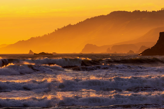 Dramatic Sunset with high tide on the beach with view of mountain range in San Francisco, Pacific Ocean California, USA