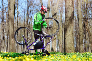 Cyclist in the spring park repairing his bicycle