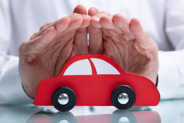 Businessman's Hand Protecting Red Toy Car