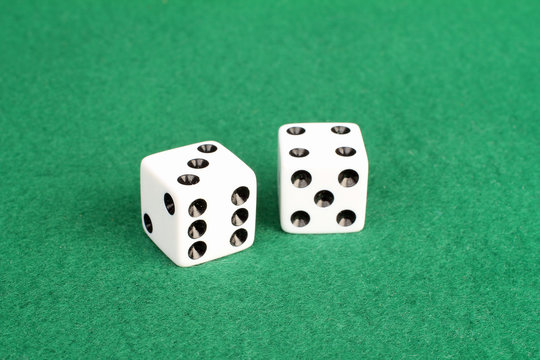 Pair of white dice on green felt with winning numbers seven and eleven showing