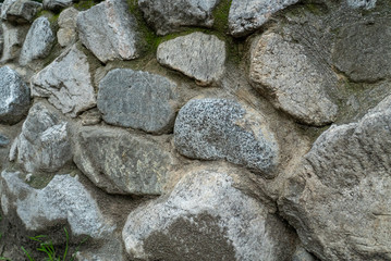 Detail of wall made of boulders with moss growing on overcast day