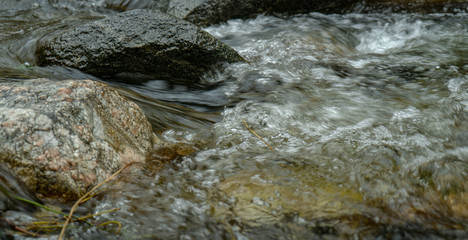 Detail of rocks in shallow stream with water flowing and bubbling over and around them.