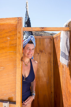 woman peeking out of outdoor shower