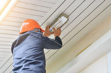 Electrician man working on exterior LED light ,replacing or changing lamp at home. Maintenance concept.