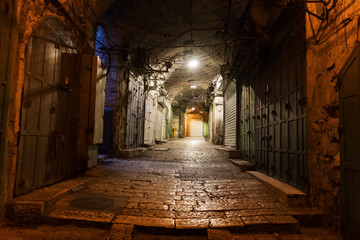 Narrow cobbled street in old medieval town with illuminated houses and pavement. Night shot of side passage in some ancient castle. Closed doors, stone paving and hanging lights in the street. Fotomurales