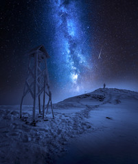 Fototapete - Milky way over a man in winter mountains