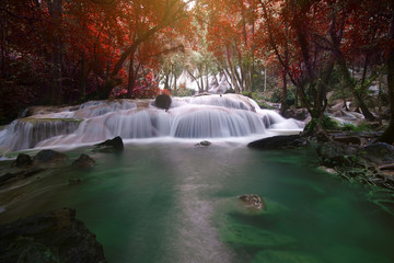 waterfall red leaves with clear green emerald water and rock for relax and refreshing cool with tree in jungle or forest at Pha Tat waterfall for nature landscape on autumn summer with sunlight