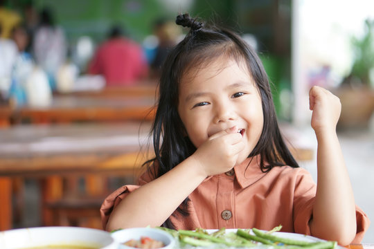 Asian child hungry or kid girl enjoy eating vegetable and delicious food on wood table with happy smiling for morning breakfast or lunch in restaurant or nursery preschool and kindergarten food court