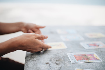 Woman is reading Tarot cards at the beach