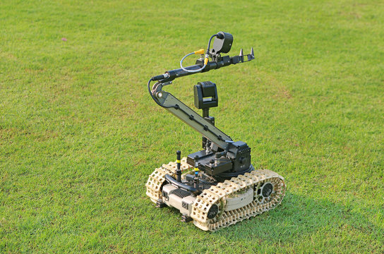 Bomb detection and disposal robot on green grass field.