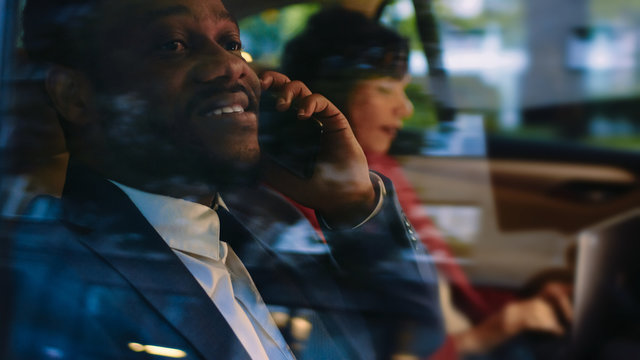 Beautiful Businesswoman and Handsome Businessman Riding on the Backseat of a Car in the Evening. Man Makes a Phone Call, Woman Works on a Laptop. Shot made from Outside the Car.