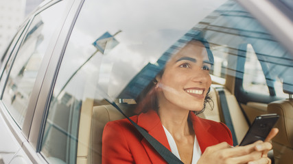 Beautiful Woman Traveling in a Car, Sitting on a Passenger Seat Uses Smartphone, types Message, Browses Through Internet. Camera Shot from Outside the Vehicle. Wall mural