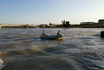 Iraqi rescuers search for survivors over the site where an overloaded ferry sank in the Tigris river near Mosul in Iraq
