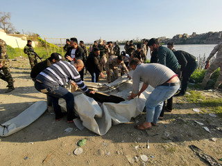 Iraqi rescues are seen near the site where an overloaded ferry sank in the Tigris river near Mosul