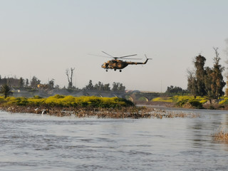 An Iraqi rescue helicopter searches for survivors at the site where an overloaded ferry sank in the Tigris river near Mosu