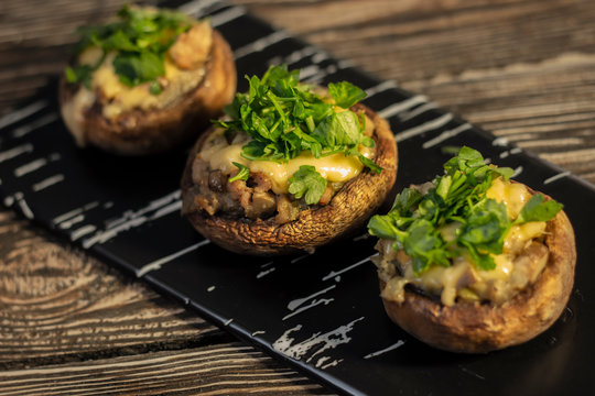 Stuffed mushrooms on a rough wooden surface