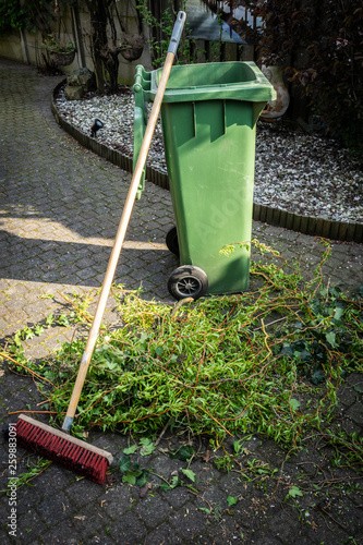 Green wheelie bin / garden waste container and broom filled with