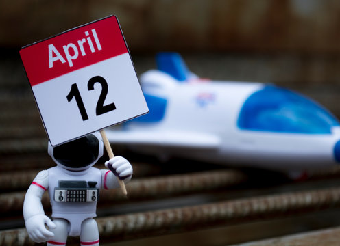 """The toy astronaut is holding a sign """"April 12"""" on the background of the shuttle. Happy Cosmonautics Day"""