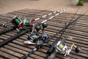 Fishing rods, spinning rods with fishing line on a wooden background in the morning light. Fishing.