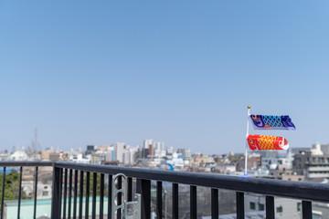 青空の下のミニチュア鯉のぼりと東京の町並み