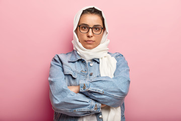 Serious confident beautiful Muslim woman obeys modesty rules, wears headscarf, fashionable denim jacket, has Islamic beliefs, keeps arms folded over chest, looks with self assuarance at camera
