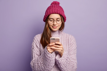 Attractive woman in stylish winter outfit, uses new gadget for positng update in internet, focused in screen, reads news online, poses over purple background. People, spare time and technology concept